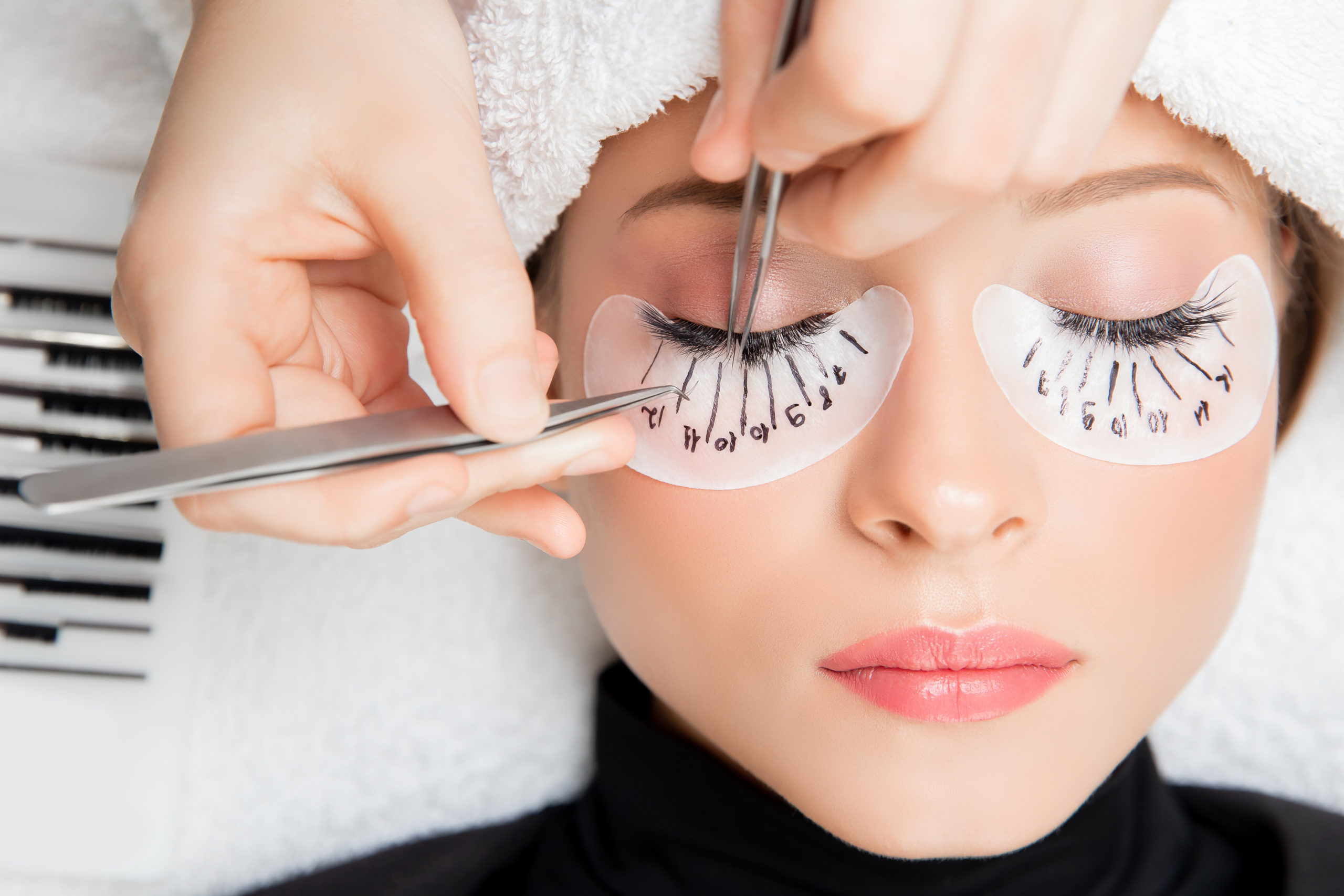 Eyelash extension procedure. Master tweezers fake long lashes beautiful female eyes.