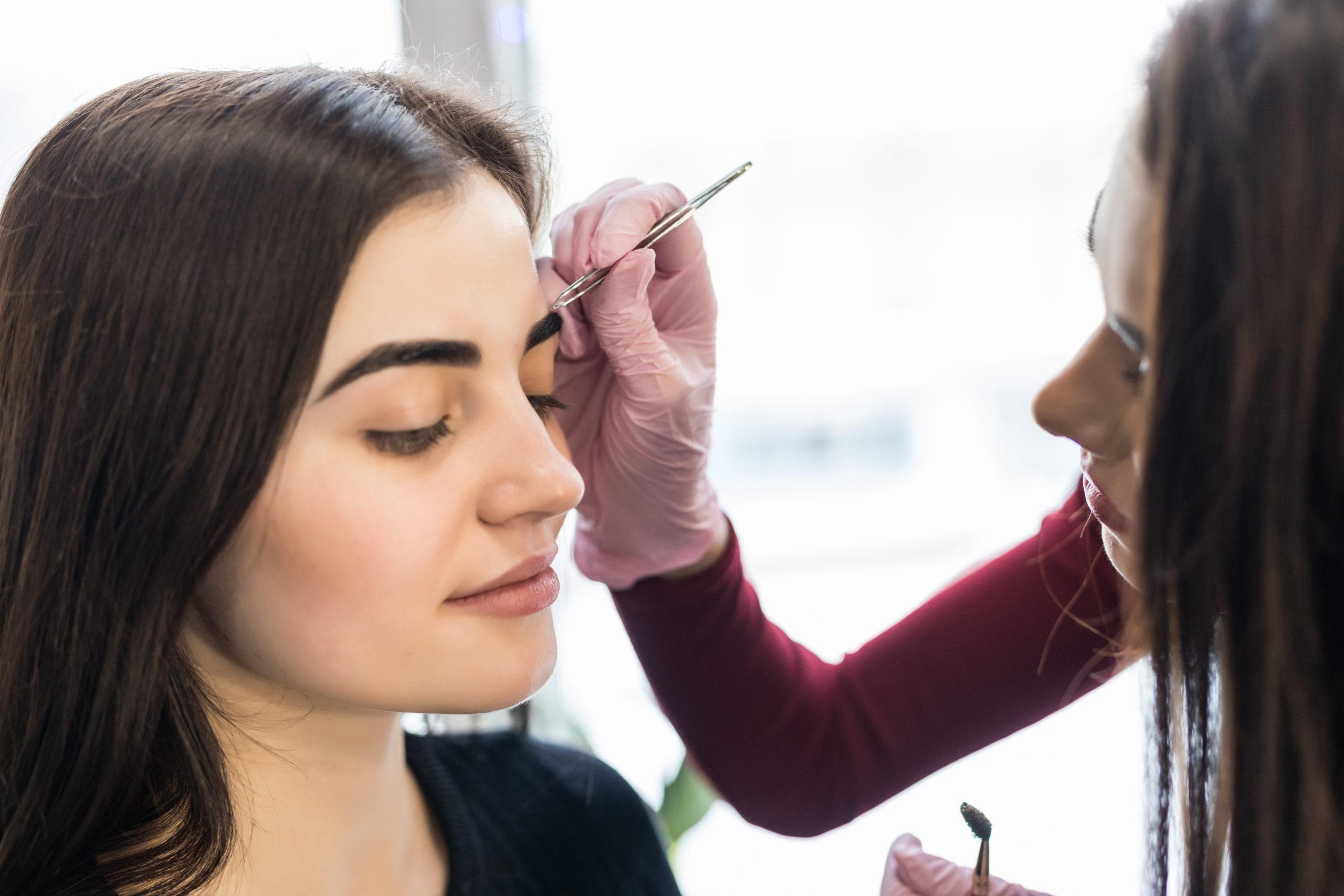 Master in white gloves work at balck eyebrows technique in salon