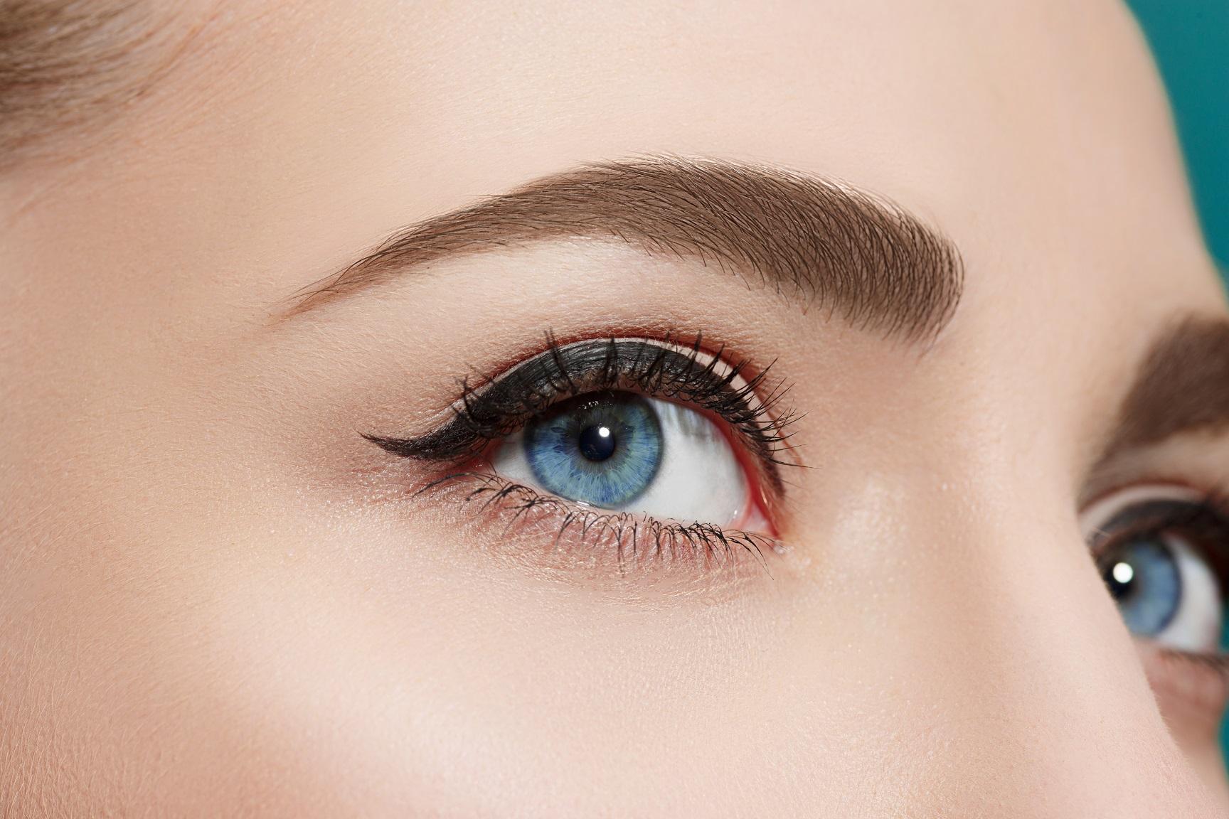 The beautiful female eye close up on blue background.